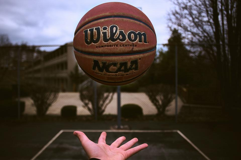 a hand tosses a basketball into the air
